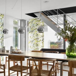 Bilden visar ljusa panelgardiner som monterats i ett kök och matrum med öppen planlösning.