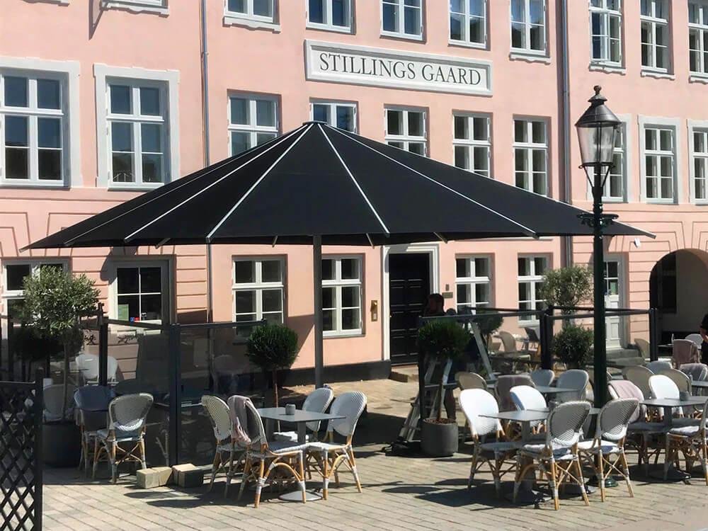 Bilden visar en 6,5 meter gånger 6,5 meter stort svart parasoll från Glatz på en uteservering.