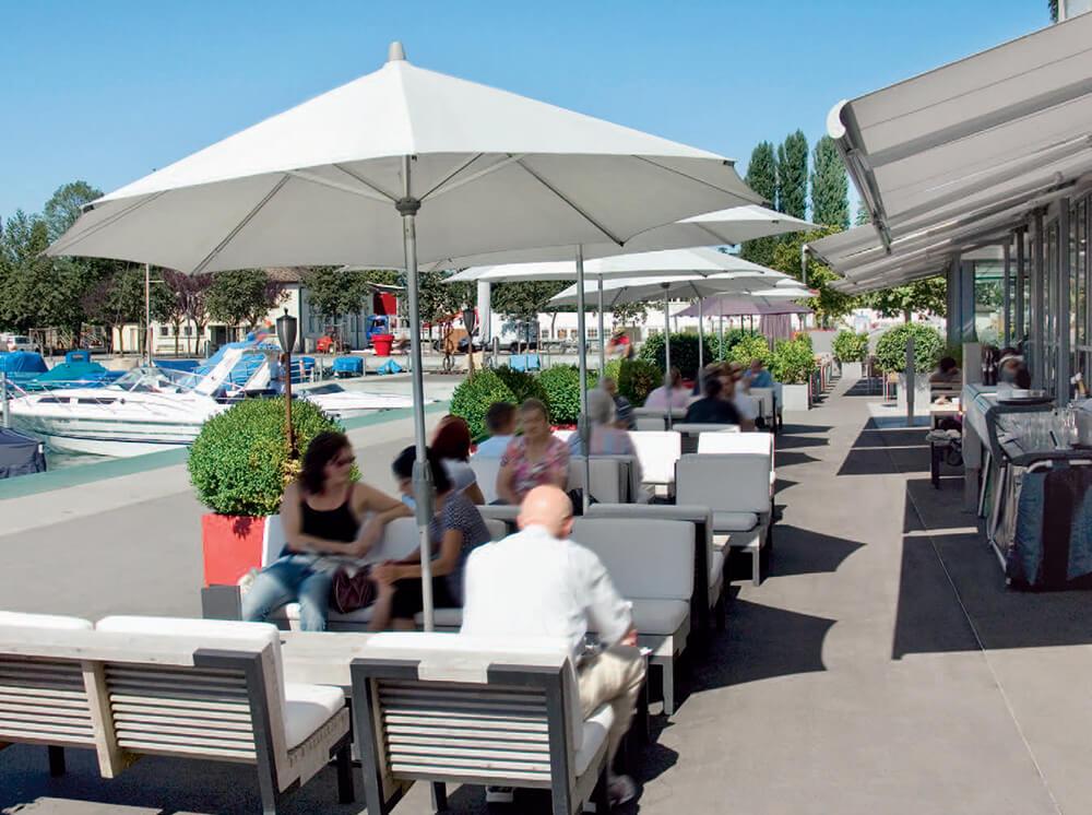 Bilden visar vita parasoller som skuggar en uteservering vid en restaurang.